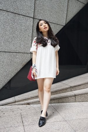 City wandering in a cute mini white dress with floral embroideries completed with a statement red sling bag and black tied-knot mules. Styled it with a twist of twilly scarf wrapped around the wrist into a bracelet.