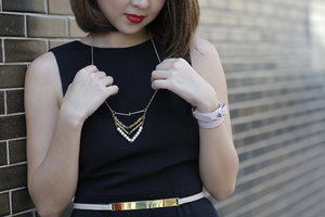 Adding a simple necklace to your black outfit to lift up the look.