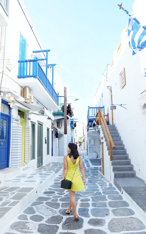 """<div class=""""photoCaption"""">Exploring the streets of Mykonos with a pop of yellow!</div>"""